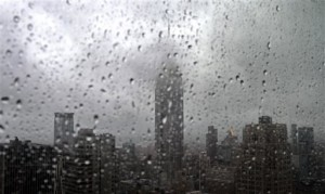 As rain covers a window with droplets, fog partially hides the Empire State building, center, in New York, Tuesday, Sept. 28, 2010. (AP Photo/Bebeto Matthews)