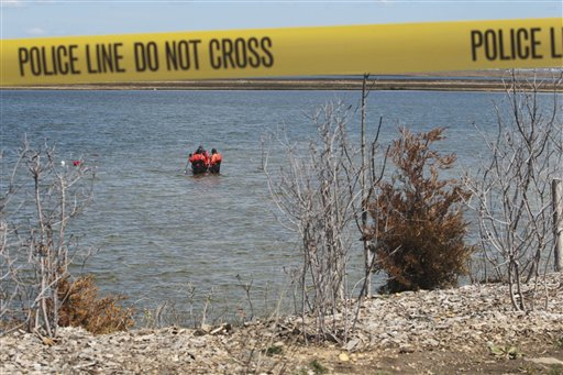 Suffolk County dive team police officers search for possible victims of a suspected serial killer in Hemlock Cove along Ocean Parkway near Cedar Beach, N.Y., Thursday, April 14, 2011. (AP Photo/Robert Mecea)