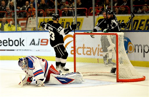 NY Rangers' goalie Henrik Lundqvist is upset after a goal by LA Kings' Mike Richards (10) during their NHL hockey match in Stockholm, Sweden, Friday, Oct. 7, 2011. Kings' Brad Richardson (15) and Dustin Brown (23) celebrate in the background. (AP Photo/Niklas Larsson)