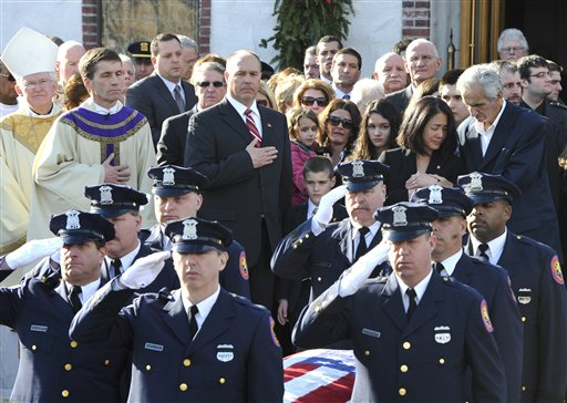 Dori Capano, back second left, wife of ATF Senior Special Agent John Capano is comforted by her father-in-law, James Capano, back far left, as son, John and daughter, Natalie, in follow as a Nassau County Police honor guard salutes Capano's casket after his funeral service at St. William the Abbott Roman Catholic Church on Friday, Jan. 6, 2012 in Seaford, N.Y. Capano, 51, was fatally shot on Dec. 31, 2011 in Seaford, N.Y. while struggling with a suspect during a robbery for painkillers and cash at a pharmacy. (AP Photo/Kathy Kmonicek)