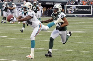 Miami Dolphins wide receiver Marlon Moore (14) catches a pass for a first down in front of New York Jets cornerback Kyle Wilson (20) during the first half of an NFL football game on Sunday, Oct. 28, 2012, in East Rutherford, N.J. (AP Photo/Bill Kostroun)