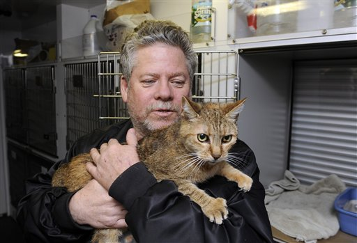 In this Oct., 28, 2012, file photo, Bill Ryan, of Inwood, N.Y., comforts his cat Amy before the arrival of Superstorm Sandy as he leaves his pet at shelter at Mitchell Park's Field House, run by the Nassau County Office of Emergency Management and Pet Safe Coalition in Uniondale, N.Y. Pet owners could drop of their pets at the shelter and afterwards seek shelter for themselves. (AP Photo/Kathy Kmonicek, File)
